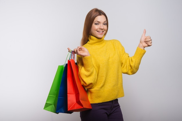 Content woman with shopping bags showing thumb up