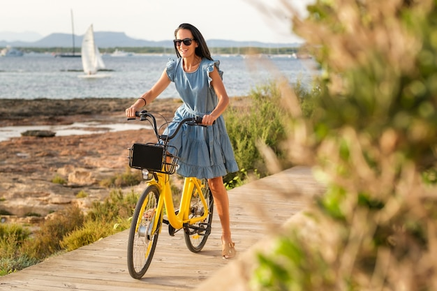 Content woman on yellow bike on promenade in summer