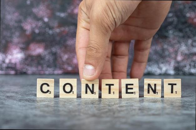 青い背景の木製のダイスに黒い文字で書くコンテンツ。高品質の写真