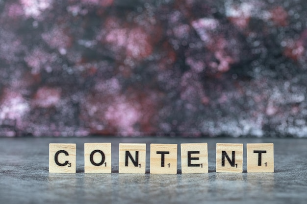 Content writing with black letters on wooden dices on blue background. high quality photo