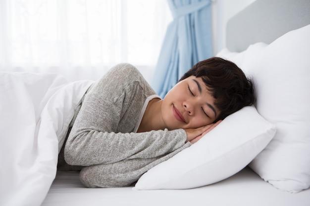 Contenuto giovane donna asiatica dorme nel letto