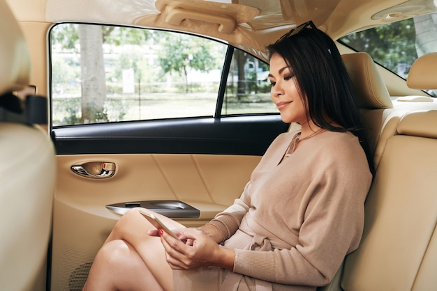 Content young asian woman with sunglasses on head sitting in car with leather interior and reading business chat on phone