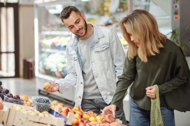 Довольная молодая пара в повседневных нарядах стоит у прилавка и ищет спелые фрукты на фермерском рынке