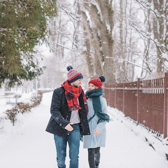 Content young couple running on snowy street
