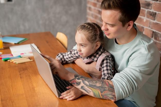 Довольный молодой отец с татуировкой на руке сидит за столом и указывает на экран ноутбука, объясняя любопытной дочери задачу обучения
