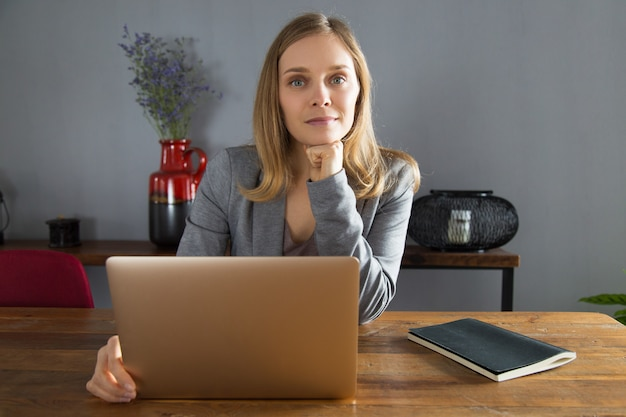 Content young female entrepreneur sitting in front of laptop