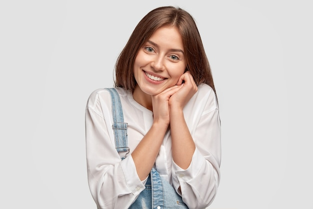 Content young female keeps hands near cheek, smiles positively, expresses happiness and truthful feelings, dressed in casual outfit