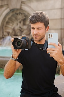 Довольный молодой парень использует смартфон и фотографирует на камеру возле фонтана