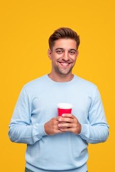 Довольный молодой парень с чашкой утреннего кофе