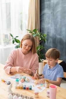 Довольная молодая мама в розовом свитере сидит за деревянным столом с художественными инструментами и делает пасхальные украшения с сыном