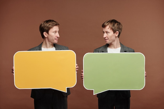 Content young twins in suits standing with speech bubble tags while exchanging messages, communication or social media concept