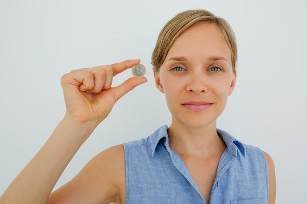 Содержание молодая женщина, держащая одну монету в евро