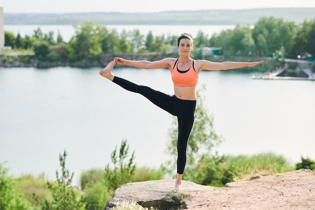 Довольная молодая женщина в спортивном бюстгальтере и леггинсах стоит на одной ноге на открытом воздухе и делает позу вытянутой руки к большому пальцу ноги