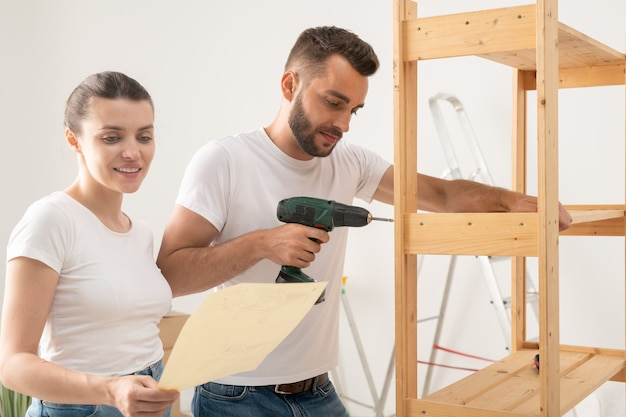 Довольная молодая женщина читает инструкцию, помогая мужу собирать мебель в новой квартире