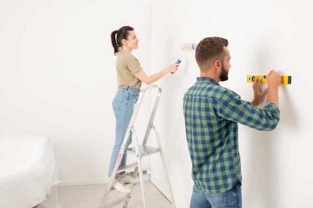 Довольная молодая женщина стоит на стремянке и красит стену, пока ее парень рисует линию с помощью уровня