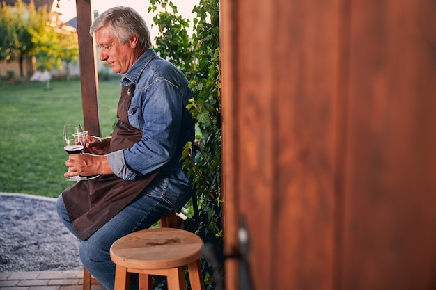 Contented adult man sitting in the yard of a winery with a decanter in hand and looking at the glass of wine with a smile