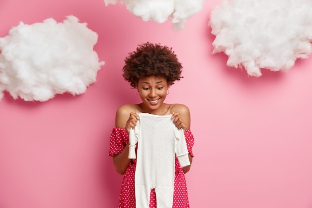 Contented afro american pregnant woman happy to buy bodysuit for future baby, anticipates for birth of child, isolated on pink wall with clouds overhead, expects small girl. pregnancy concept