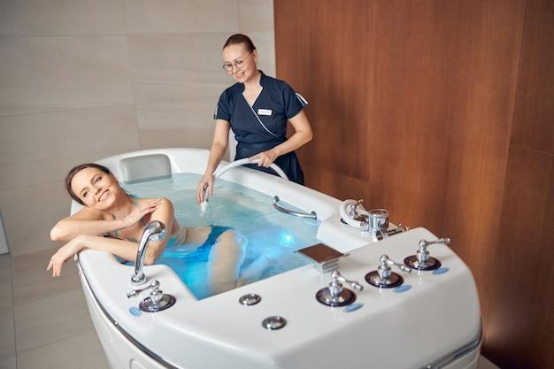 그녀의 웃는 환자에서 압력을 받고 물 제트를 지시하는 만족 백인 여성 치료사
