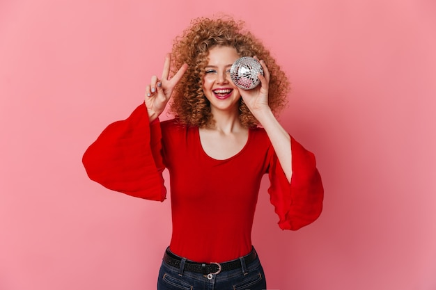 Contented curly girl smiles, shows peace sign and holds small disco ball on pink space.