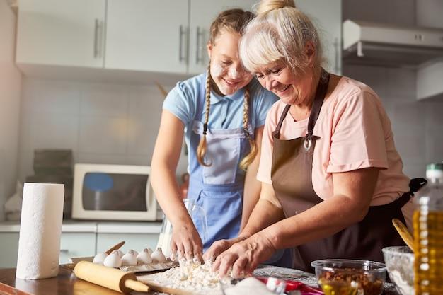 孫娘が台所で彼女を助けてくれる満足している祖母