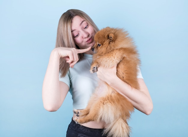 A contented happy girl gets a cute puppy, plays and lovingly hugs her four-legged friend, stands on a blue wall, wears a short t-shirt. a woman hugs a pomeranian. people and dogs