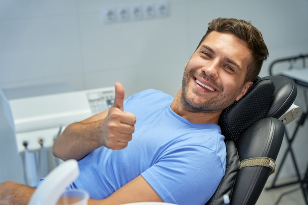 Contented patient of dental clinic showing thumbs up