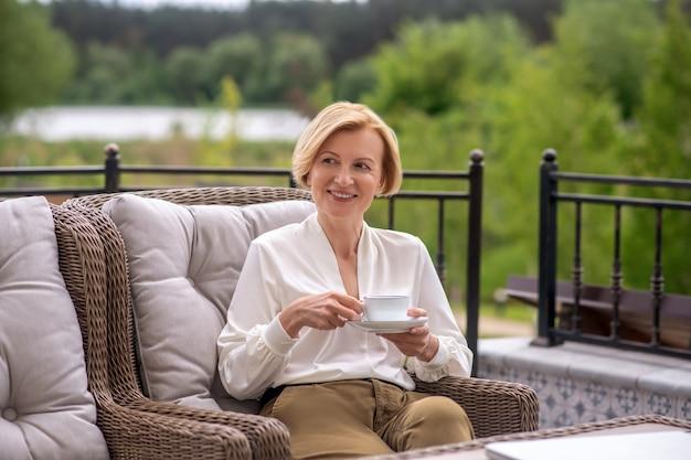 Довольная приятная аристократическая женщина наслаждается перерывом на кофе на открытом воздухе