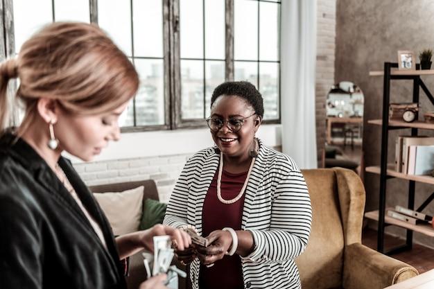 満足。積極的に笑っている縞模様のジャケットを着ているふっくらアフリカ系アメリカ人女性