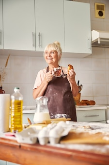 집에서 갓 구운 패스트리를 맛보며 만족한 노부인