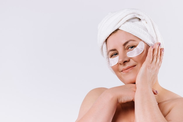 Contented senior woman posing against a white background with a towel on her head and pads under her