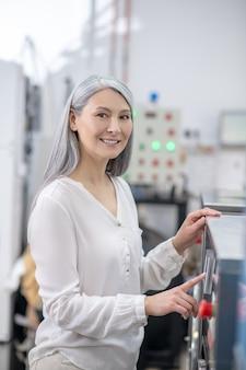그녀의 손으로 만지고 세탁기의 제어판 근처에 서있는 가벼운 옷에 만족 한 여자