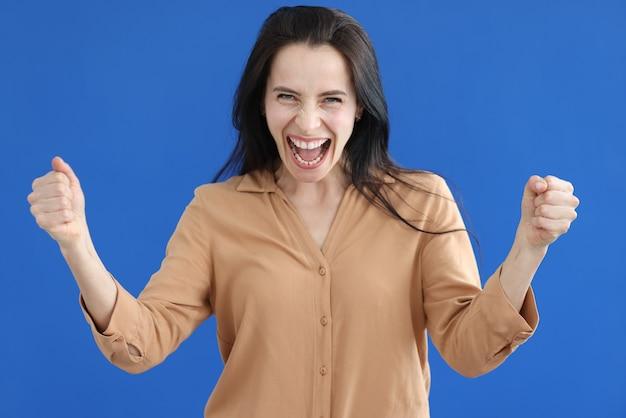 Довольная женщина со сложенными кулаками кричит на синем фоне