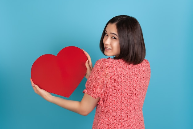 Contented young asian woman in a red dress stands with her back and holds a large red paper heart