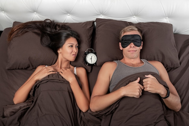 A contented young couple is lying in bed, an alarm clock lying between them
