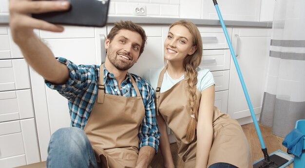 満足している若いカップルは、ハードキッチンクリーニングの後に自撮りを作る