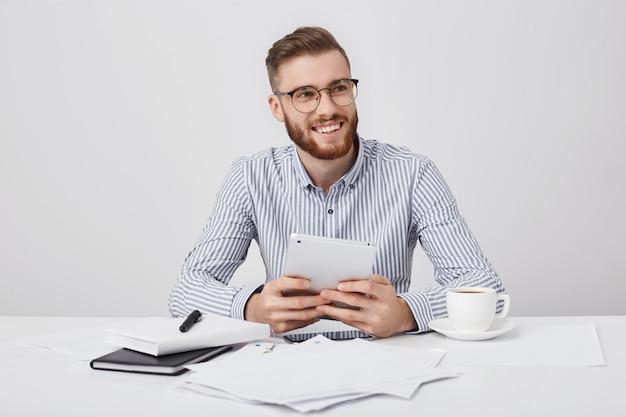 快適な笑顔で満足している若い男性のフリーランサーは、現代のタブレットを手に持っています、