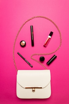 Contents of one white female bag. female bag with copy space on pink background