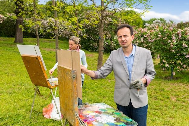 Художники-состязательные мужчины и женщины рисуют на мольбертах картины под открытым небом на фоне красивых деревьев.