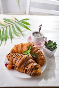 Continental breakfast freshly baked croissant decorated with jam and chocolate