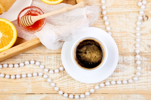 Continental breakfast on ristic wooden tray and necklace