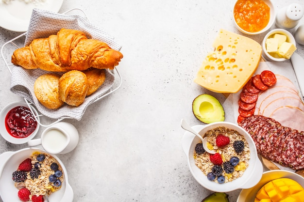 Continental breakfast table with croissants, jam, ham, cheese,  butter, granola and fruit, copy space.