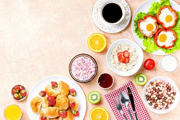 질감 있는 테이블에 시리얼, 계란 프라이, 크루아상, 과일 및 음료가 포함된 유럽식 조식이 제공됩니다. 소박한 배경에 다양한 건강 간식과 음식이 있는 탁자