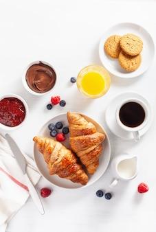クロワッサン、ジャム、チョコレートスプレッド、コーヒーを含むコンチネンタルブレックファースト。上面図