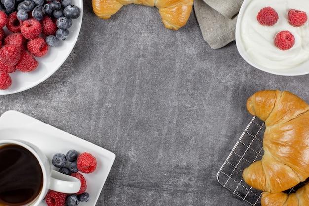 회색 콘크리트 배경에 크로와상 블랙 커피 나무 딸기와 블루 베리와 유럽식 아침 식사