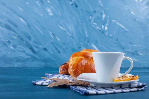 Colazione continentale con croissant freschi, una tazza di tè e limoni a fette su uno strofinaccio.