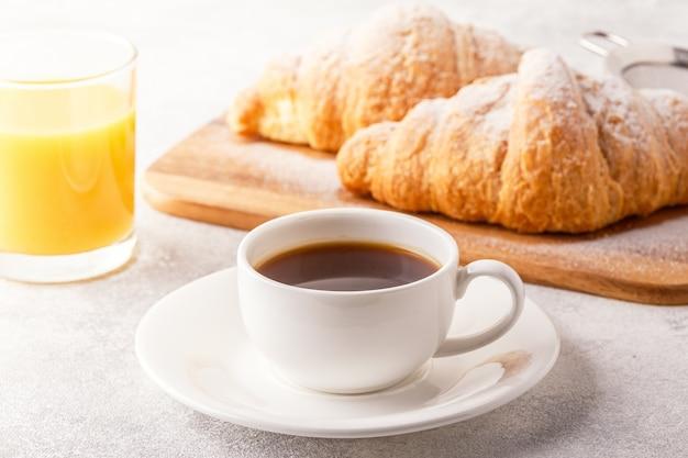 焼きたてのクロワッサン、オレンジジュース、コーヒー、セレクティブフォーカセを含むコンチネンタルブレックファースト。