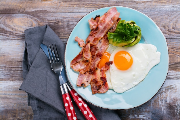 Continental breakfast with fried eggs, bacon and avocado