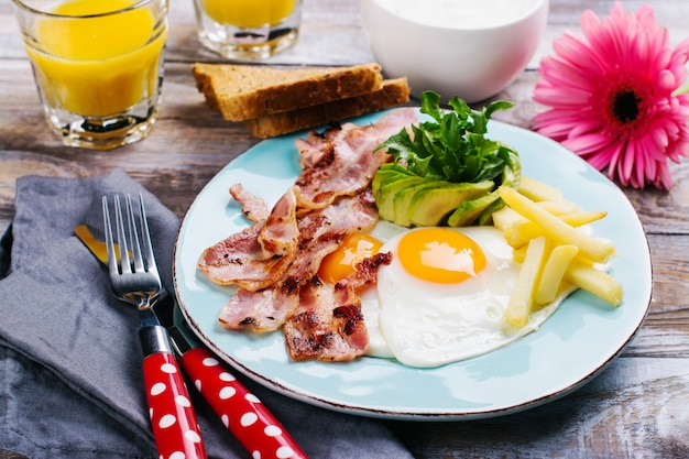 Continental breakfast with fried eggs, bacon and drinks