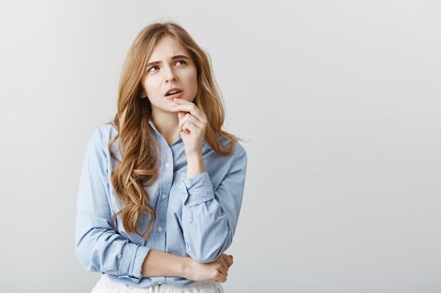 다이어트를 계속하거나 피자를 주문하십시오. 금발 머리와 곱슬 머리를 가진 의심스러운 생각 매력적인 여자의 초상화, 입술을 만지고 사려 깊은 집중된 표정으로 찾고, 회색 벽에 아이디어를 가지고