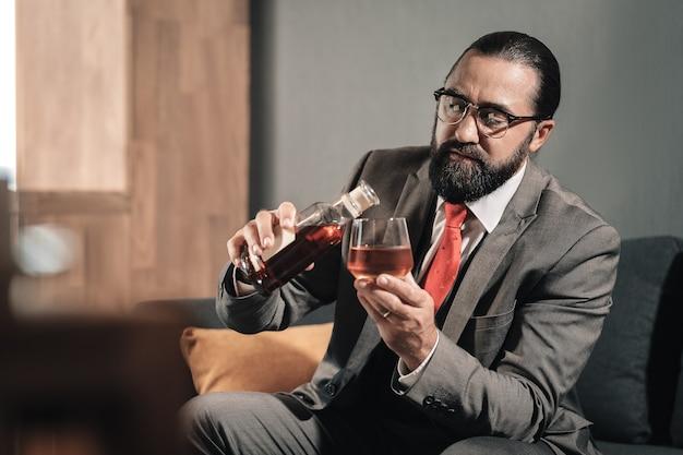 飲み続けます。ウイスキーを飲み続けている神経衰弱に苦しんでいるひげを生やした男